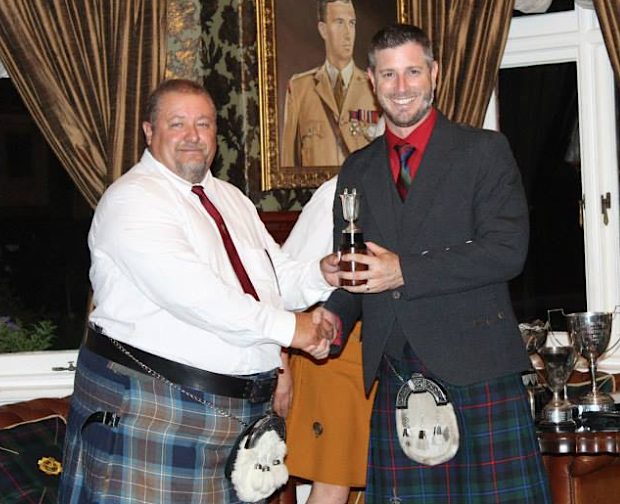 Champion piper Gareth Rudolph receives his trophy
